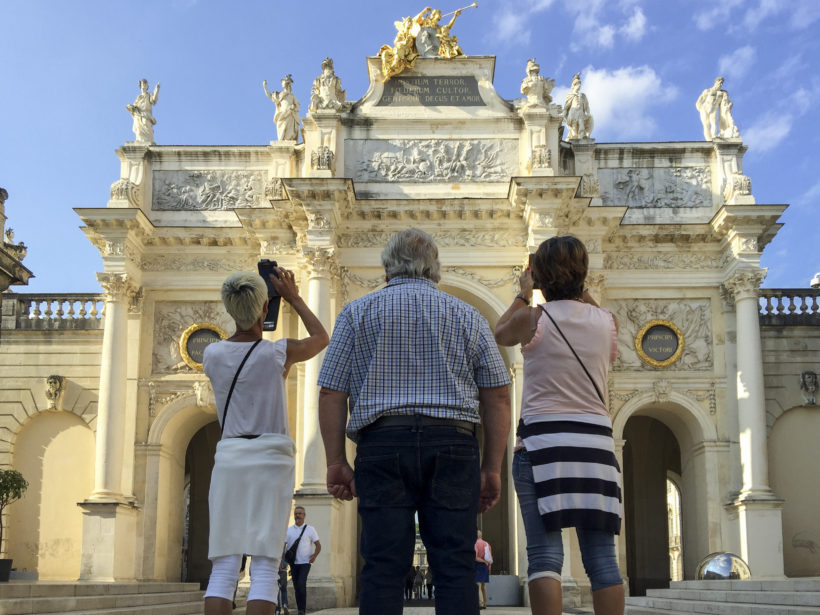 Tourists taking photos of the Arc Héré